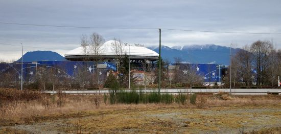 Looking north across undeveloped freeway lands to the Colossus Cinema and the Golden Ears peaks.