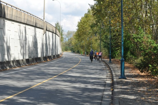 Argue Street, closed to through vehicle traffic, under the embankment of provincial highway 7B. The Fraser River is on the right.