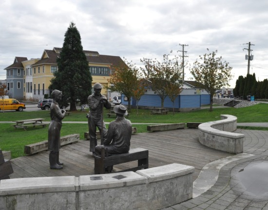 A grouping of statues of fish cannery workers outside the Cannery museum. The two-storey building in the background is recent.